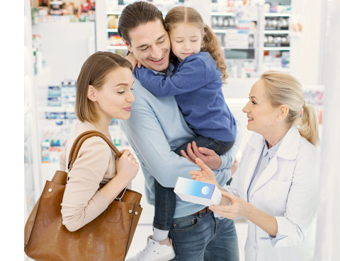 pharmacist showing pharmacy product to a family customer