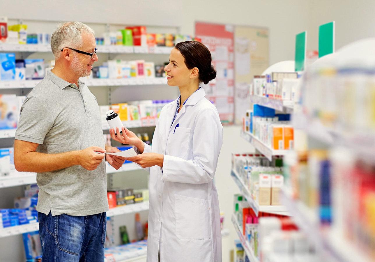 pharmacist handing a medecine to a senior man