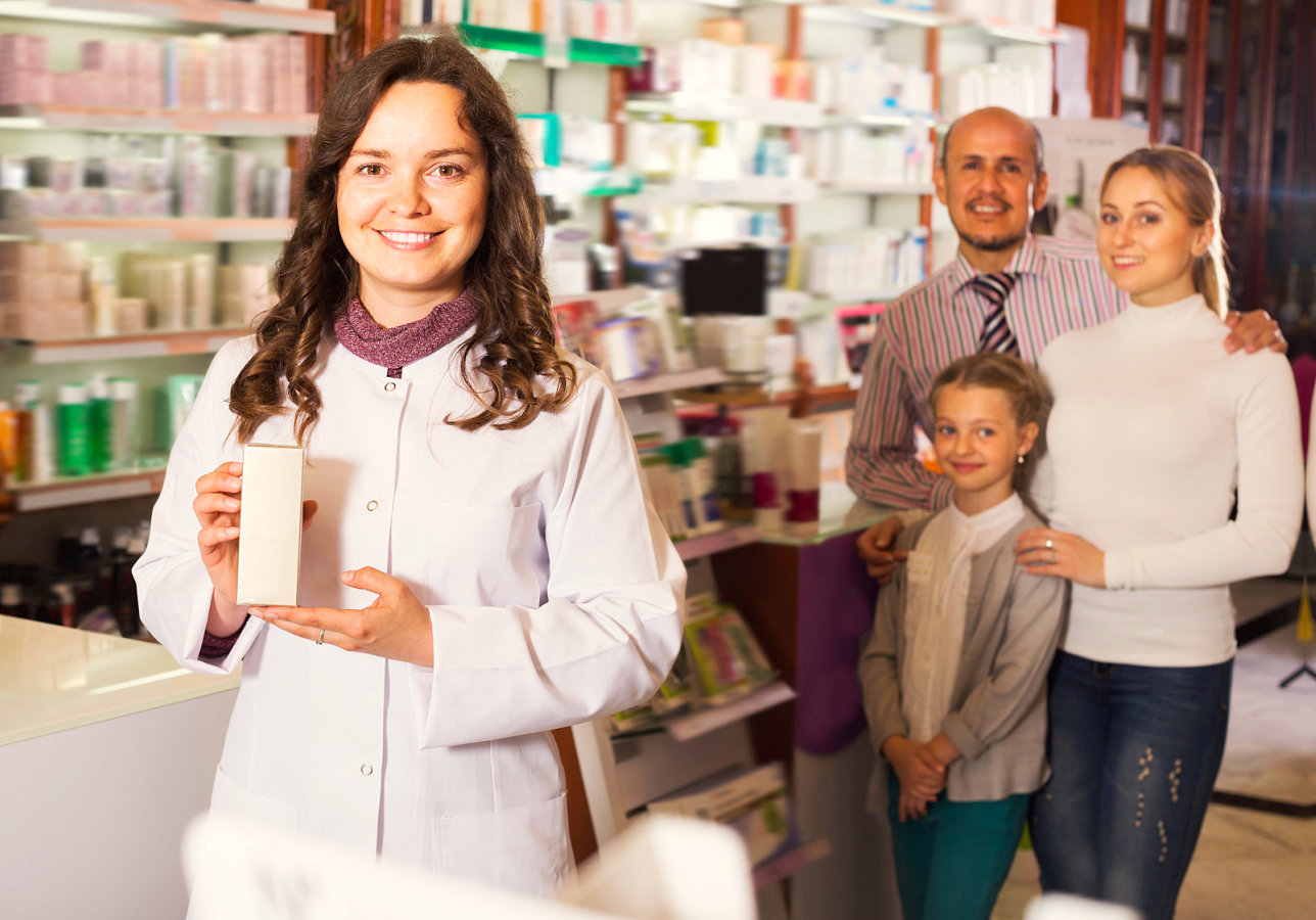 pharmacist showing a product with a couple with their daughter on the background
