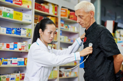 female pharmacist checking on senior man