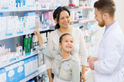 male pharmacist, mother and her daughter smiling
