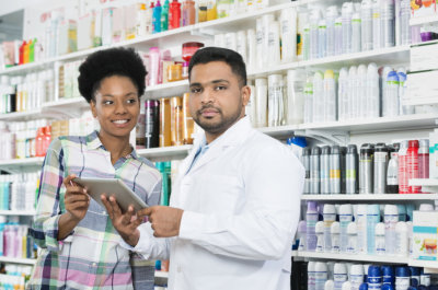 male pharmacist and female customer smiling